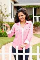 Young Hispanic woman outside new home