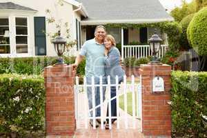 Senior Hispanic couple outside home