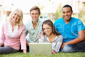 Young people using laptop outdoors