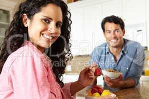 Hispanic couple eating cereal and fruit