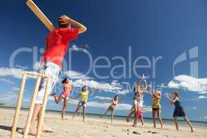 Teenagers playing cricket on beach