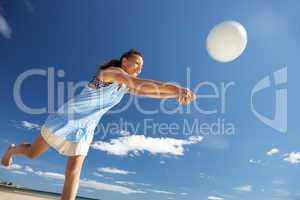 Teenage girl playing beach volleyball