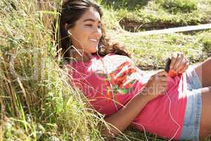 Teenage girl using mp3 player outdoors