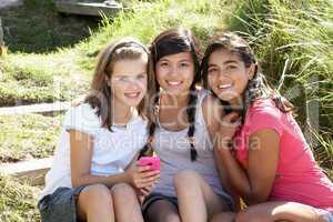Teenage girls using phone outdoors
