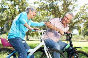 Senior couple playing on children's bikes
