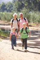 Senior couple and grandchildren on country walk