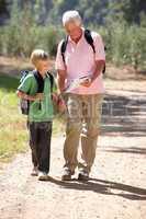 Senior man and grandson on country walk