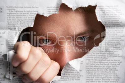 Man looking through hole in newspaper
