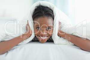 Smiling woman covering her ears with a duvet