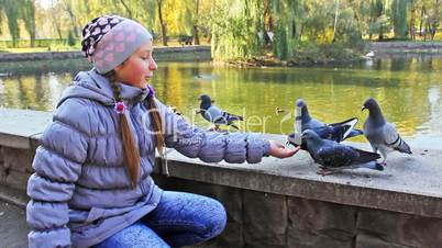 Girl Siting Feeds Pigeons From Hand