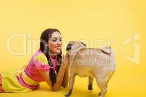 Happy wwoung woman in doll dress feed a small dog