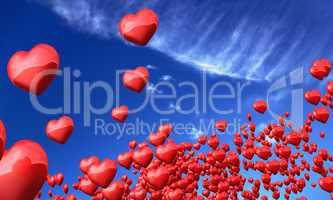 Fliegende rote Herzen vor blauem Himmel