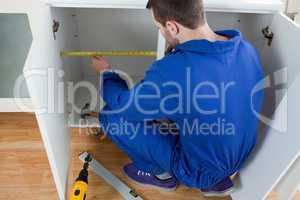 Young repair man measuring something