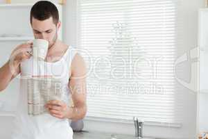 Man drinking tea while reading the news