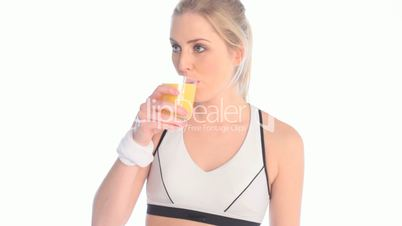 blonde fitness woman drinking orange juice after workout