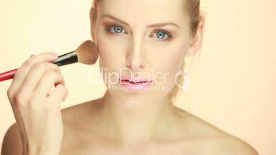 blonde woman applying blusher