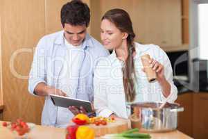In love couple using a tablet computer to cook