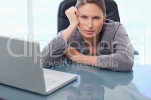 Serious businesswoman leaning on her desk