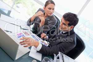 Business team studying statistics with a laptop