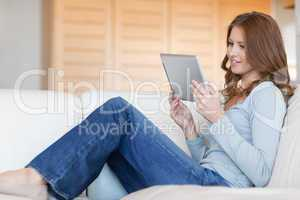 Woman reading e-book on the sofa