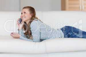 Young woman on the sofa having a nice conversation on the phone
