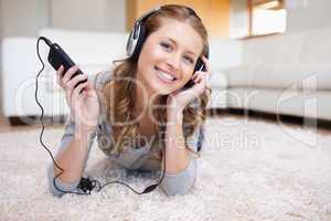 Woman lying on the floor enjoying music