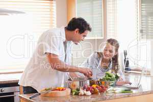 Couple using laptop to look up recipe for their meal