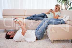 Woman using her phone while her boyfriend is using a tablet comp