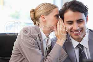 Young businesswoman whispering something to her colleague