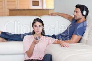 Woman watching television while her boyfriend is listening to mu