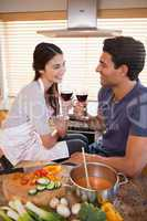 Portrait of a happy couple having a glass of wine while cooking