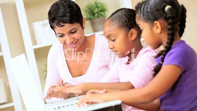 Mutter und Töchter mit dem Laptop