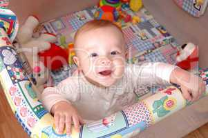 Smiling child playing in the cot, family scenes
