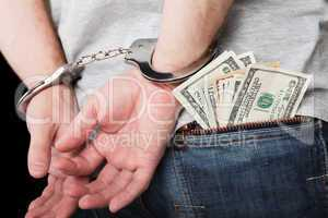 Handcuffs on hands hiding money