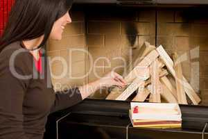 Home fireplace woman lighting up wooden logs