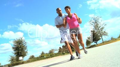 Young Ethnic Couple Training on Suburban Roads