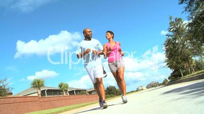 Ethnic Female Jogging with Personal Trainer