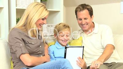 Attractive young family using a wireless tablet to talk to family and friends using online web chat