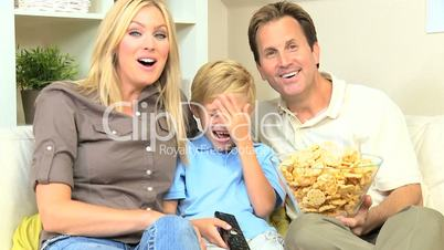 Attractive Family Enjoying TV & Snack Food