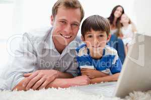 Boy with his father using laptop on the carpet