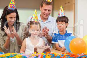 Parents applauding her daughter who just blew out the candles on