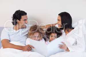 Family reading a story in the bedroom