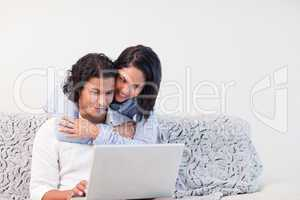 Couple spending time online in the living room together