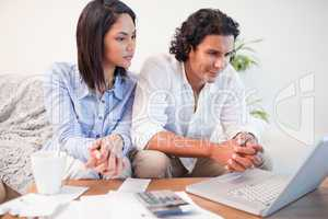 Couple sitting in the living room doing online banking