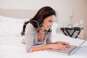 Woman lying on the bed surfing the internet