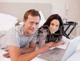 Happy couple using laptop on the bed together