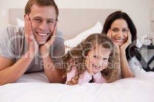 Smiling family lying on the bed together