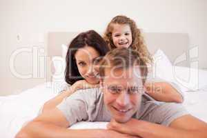 Playful family spending time in the bedroom