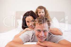 Joyful family having a good time in the bedroom