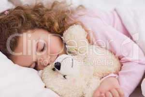 Girl hugging her teddy while sleeping